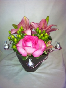 A milk chocolate ceramic container holding pink flowers and even chocolate kisses for only 55.95